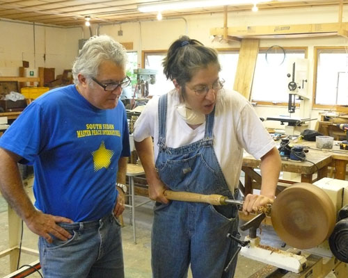 Paul Maserjian gets some pointers on wood turning from instructor Theo Fidel