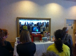 Friends viewing photos of Andrea Raphael at today's memorial service at the Log Cabin.