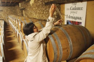 Laurance, proprietor at Ch Millet, pulls a taste from the cask.