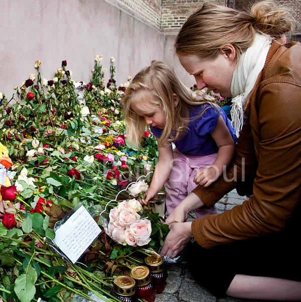 a youg girl and her mother place a flower out side of the  Oslo Cathedreal in Norway