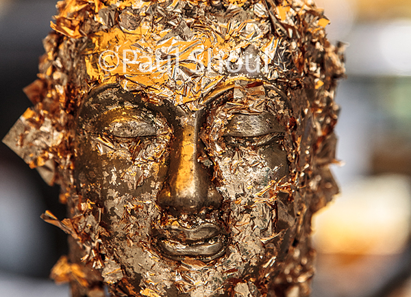 grand palace in Bangkok Thailand gold leaf on the face of a buddha statue