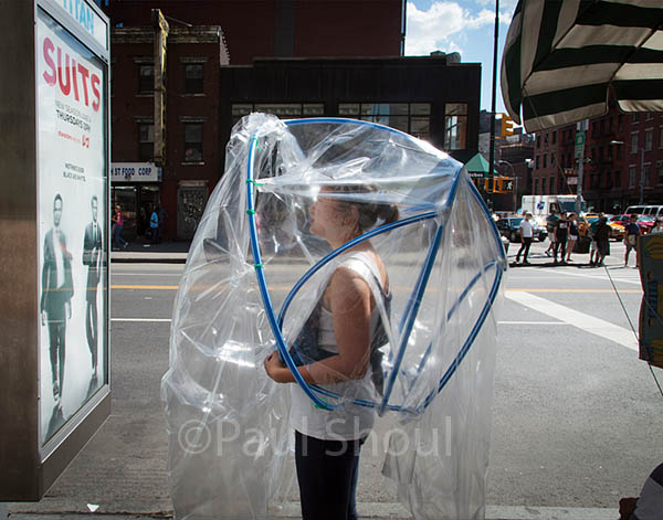 New york city , a woman covered in a plastic bubble suit stares at a suits poster