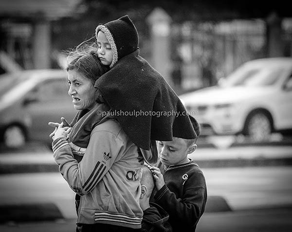 Bogota Colombia a woman waits with three children wraped around her to cross rush hour traffic