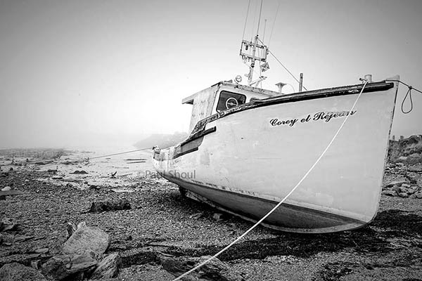 a wooden boat on the shore,yarmouth Nova Scotia foggy day in black and white