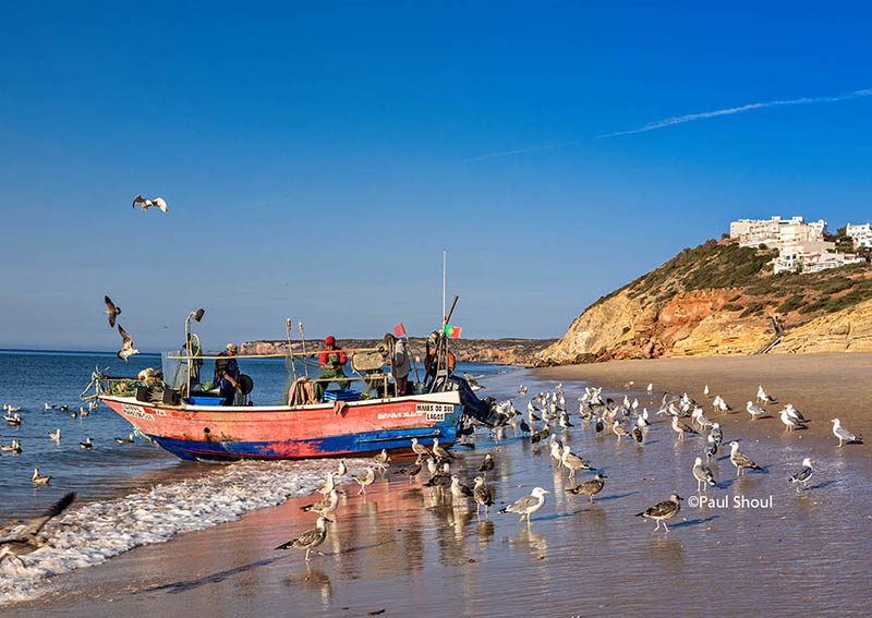 Fishing boat on the beach cleanig nets salema algarve portugal