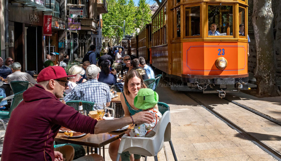 The famous wooden train of Soller pass through a crowded town in Mallorca,Spain.